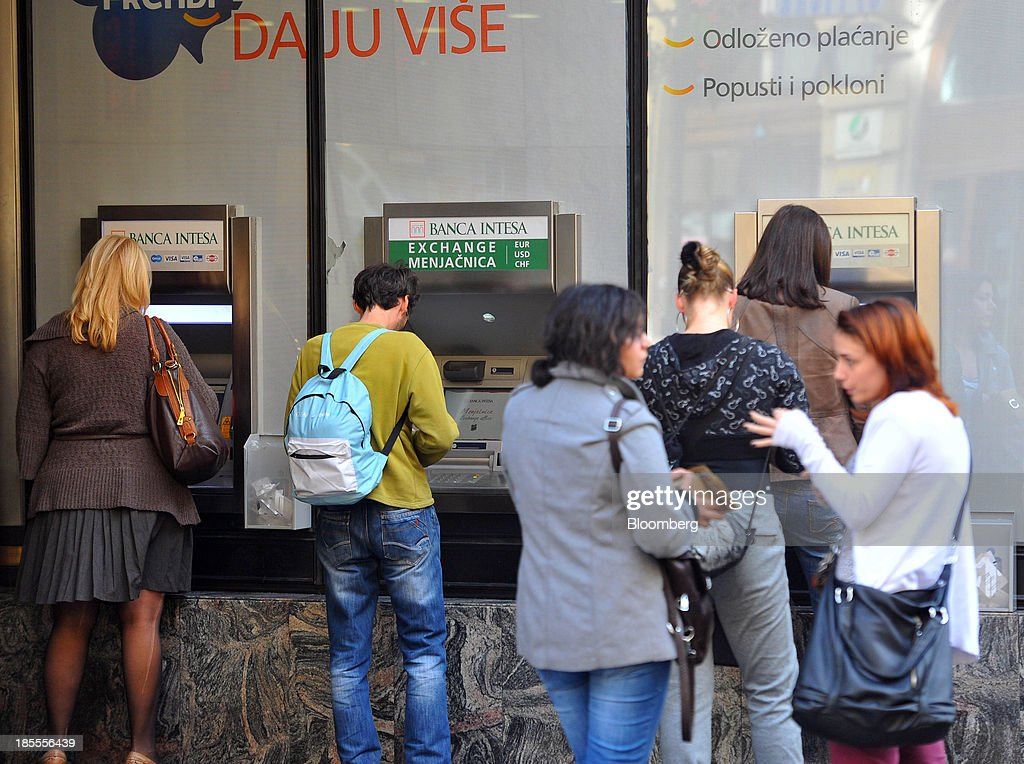 Customers use automated teller machines (ATM) outside a Banka Intesa SpA branch in Belgrade, Serbia, on Monday, Oct. 21, 2013. Serbia's government revealed a salvo of measures to bring the public finance deficit and debt back under control by 2017 after the head of the largest coalition party warned the country was on the brink of insolvency. Photographer: Oliver Bunic/Bloomberg via Getty Images