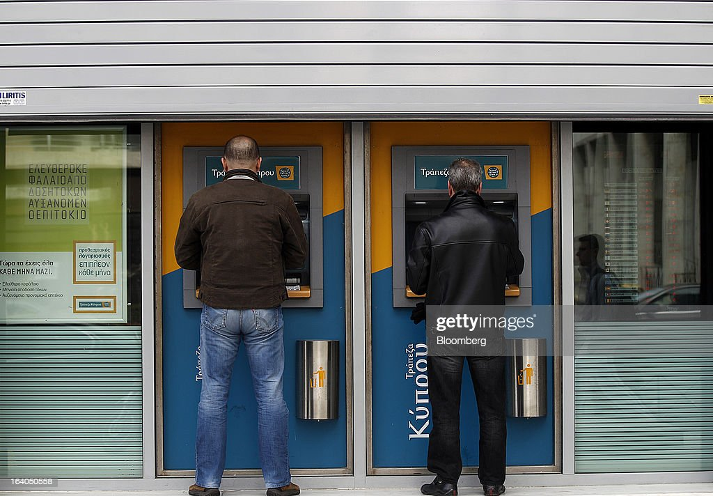 Customers use automated teller machines (ATM) outside a closed bank branch at the headquarters of the Bank of Cyprus Plc in Athens, Greece, on Tuesday, March 19, 2013. Cyprus's passage of an unprecedented levy on bank deposits was in doubt as euro-area finance ministers responded to criticism of the measure by loosening their stance on how the money is raised. Photographer: Kostas Tsironis/Bloomberg via Getty Images