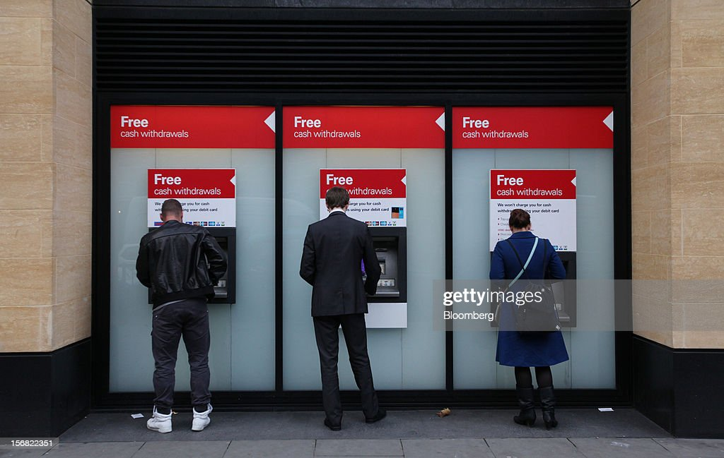 Customers use automated teller machines (ATM) outside a HSBC Holdings Plc bank branch in London, U.K., on Thursday, Nov. 22, 2012. Shares of HSBC have climbed 26 percent this year in London trading, and 30 percent in Hong Kong, as Chief Executive Officer Stuart Gulliver pared costs and sold assets to revive profit and focus on emerging economies in which the bank has a greater market share. Photographer: Chris Ratcliffe/Bloomberg via Getty Images