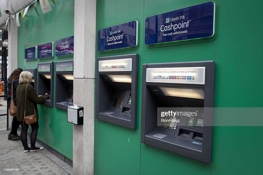 Customers use automated teller machines (ATM) outside a Lloyds TSB bank branch, part of the Lloyds Banking Group Plc, in London, U.K., on Wednesday, July 18, 2012. The U.K. financial regulator said it's investigating seven lenders over attempts to manipulate interbank offered rates as lawmakers criticized it for not opening the probe earlier. Photographer: Simon Dawson/Bloomberg via Getty Images