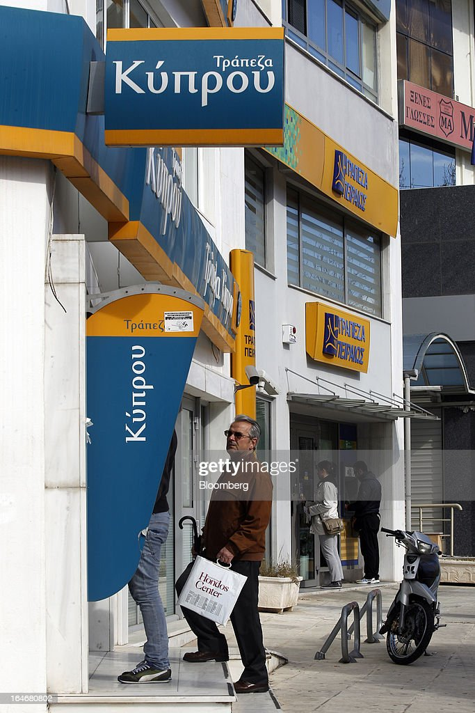 Customers use automated teller machines (ATM) outside Bank of Cyprus Plc, left, and Piraeus Bank SA, right, branches in Athens, Greece, on Tuesday, March 26, 2013. Piraeus Bank SA acquires Greek units of Cypriot lenders for total cash consideration of EU524m, according to e-mailed statement from the Athens-based lender today. Photographer: Kostas Tsironis/Bloomberg via Getty Images
