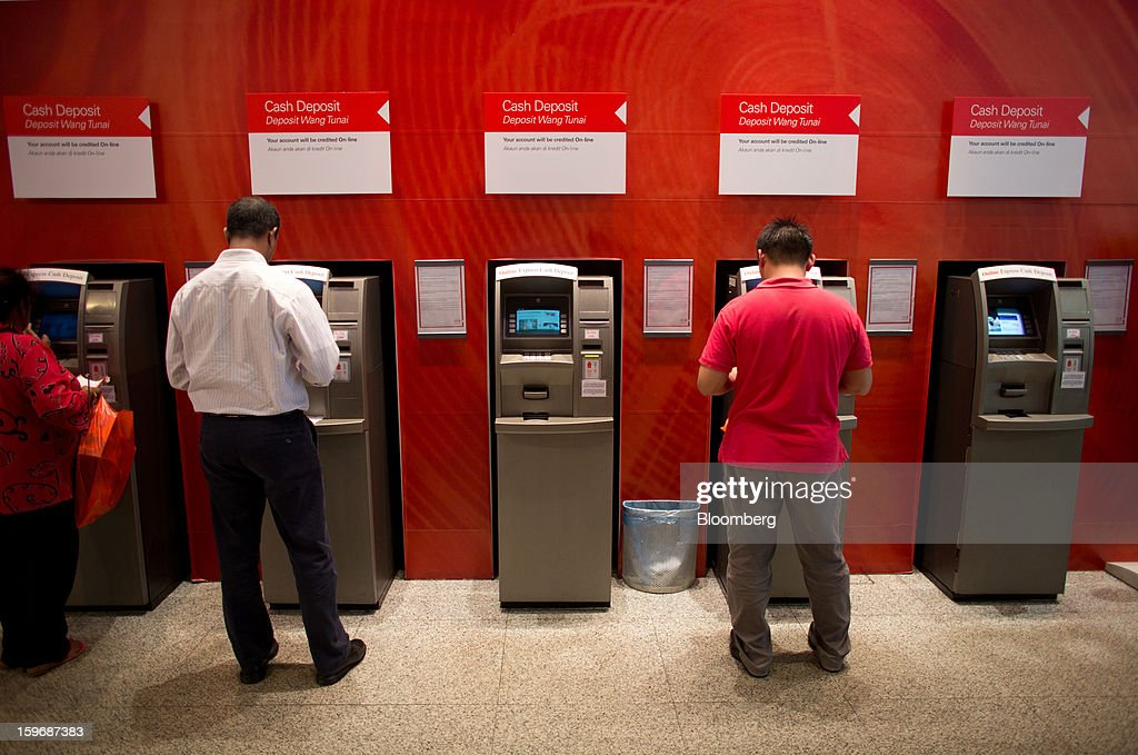 Customers use cash deposit machines at an HSBC Holdings Plc bank branch in Kuala Lumpur, Malaysia, on Wednesday, Jan. 16, 2013. While many developed countries have faltered, Malaysia's gross domestic product growth has exceeded 5 percent for five quarters with domestic demand countering a slowdown in exports. Photographer: Lam Yik Fei/Bloomberg via Getty Images