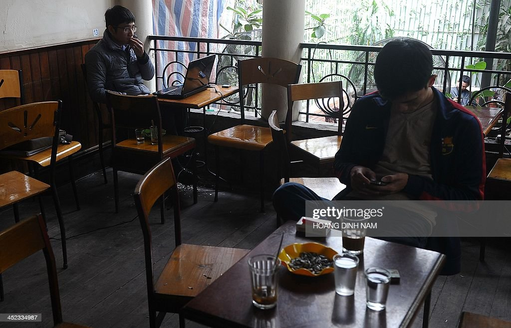 Customers use computers and other wifi devices at a coffee shop in downtown Hanoi on November 28, 2013. Vietnam has intensified a crackdown on online dissent with a new decree that threatens fines of several thousand dollars for anybody criticising the government on Facebook.