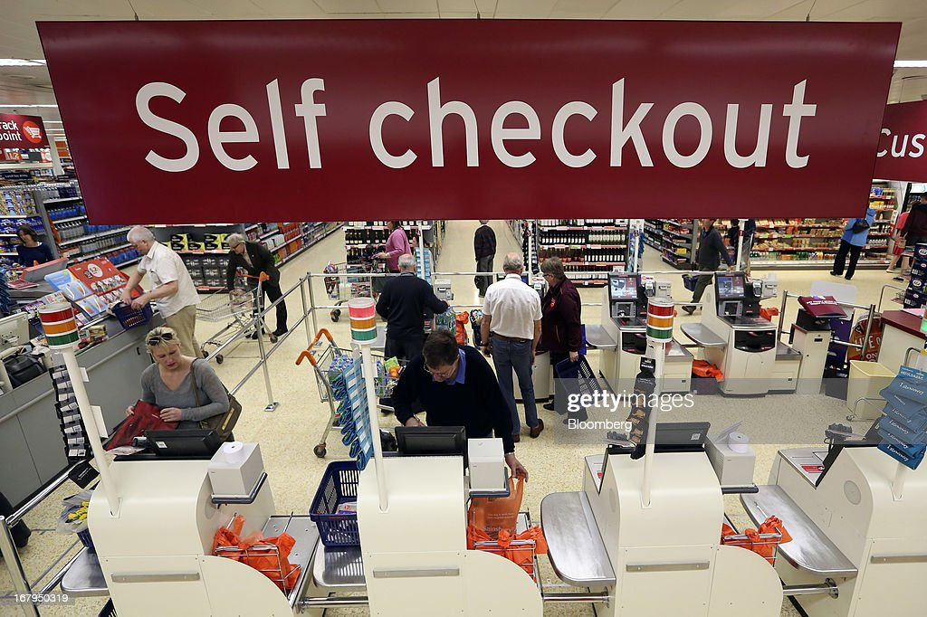 Customers use self checkout desks to pay for goods after shopping inside a Sainsbury's supermarket store, operated by J Sainsbury Plc, in Godalming, U.K., on Thursday, May 2, 2013. J Sainsbury Plc, the U.K.'s third-largest supermarket chain, will report full year results on May 8. Photographer: Chris Ratcliffe/Bloomberg via Getty Images