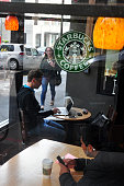 Customers use their laptop computers and mobile devices in a Starbucks coffee shop in San Francisco California