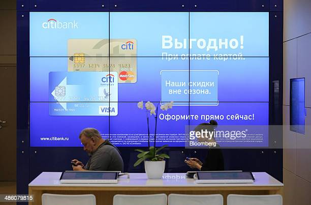 Customers use their mobile phones while waiting for service beside a digital advertisement for Mastercard Inc and Visa Inc payment cards inside a...