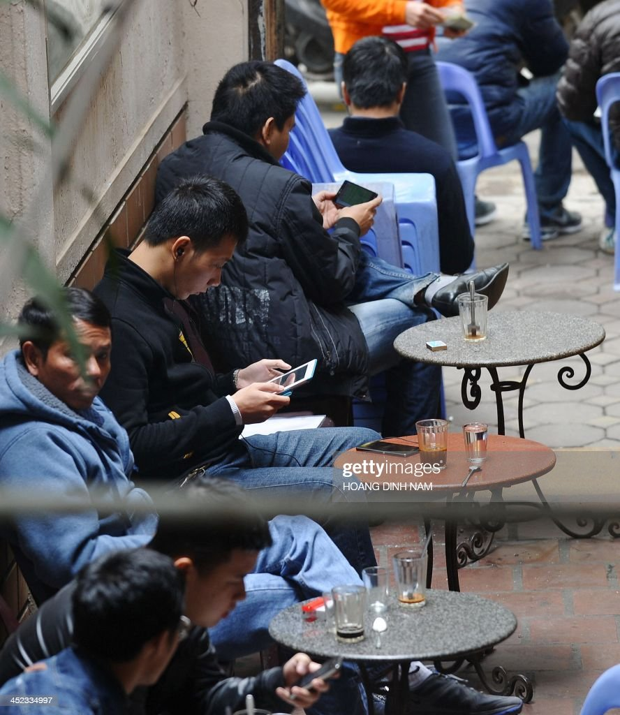 Customers use wireless devices at a coffee shop in downtown Hanoi on November 28, 2013. Vietnam has intensified a crackdown on online dissent with a new decree that threatens fines of several thousand dollars for anybody criticising the government on Facebook.