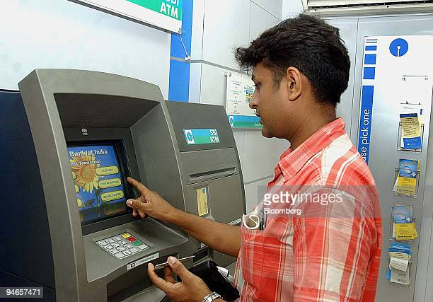 A customers uses an ATM machine to withdraw cash inside a branch of the State Bank of India at Nariman Point Mumbai on Tuesday July 11 2006 Indian...