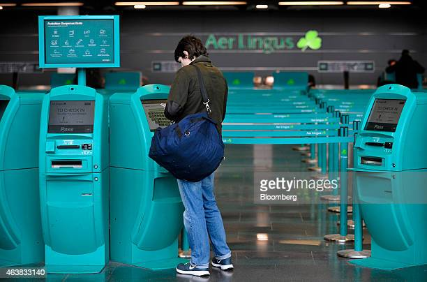 A customers uses an automated self checkin machine near the Aer Lingus Group Plc checkin desk in the departure hall at Dublin Airport operated by...