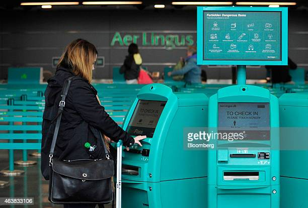 A customers uses an automated self service checkin machine near the Aer Lingus Group Plc checkin desk in the departure hall at Dublin Airport...