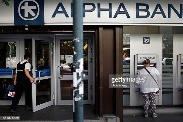 Customers uses automated teller machines as a security guard carries a cash box into an Alpha Bank AE bank branch in Athens Greece on Monday July 20...