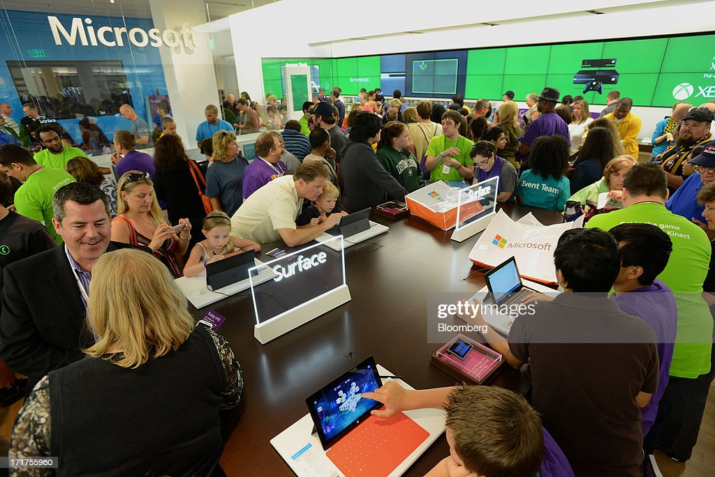 Customers view products on display during the grand opening of a Microsoft Corp. store in Troy, Michigan, U.S., on, Friday, June 28, 2013. Microsoft, which has been struggling with the inability of outside retailers to effectively display its products, aims to generate more enthusiasm for them by opening its own stores. Photographer: Bryan Mitchell/Bloomberg via Getty Images