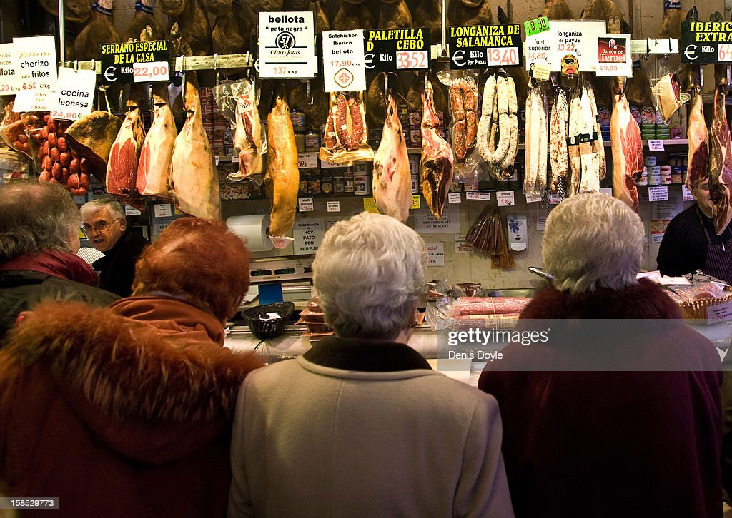 Customers wait at the counter of the Ferpal ham store on Calle Arenal on December 18, 2012 in Madrid, Spain. Dry-cured Iberian ham or Jamon Iberico is a favourite amongst Spaniards and producers are hoping for improved sales over the busy Christmas period. The jamon Iberico de Bellota are usually dry-cured for up to three years after the pigs have been few on a diet of acorns in the last three months of their lives.
