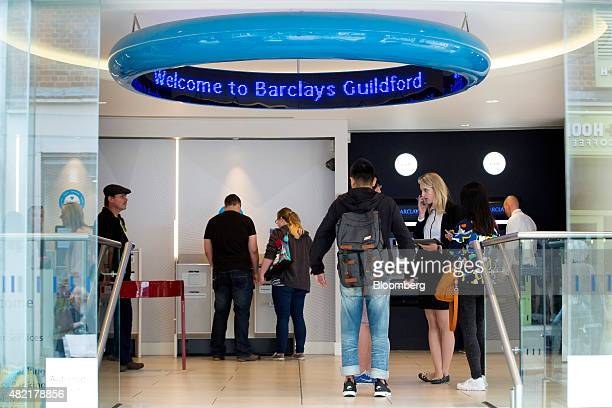 Customers wait for service from an employee inside a Barclays bank operated by Barclays Plc in Guildford UK on Monday July 2015 Barclays Plc should...