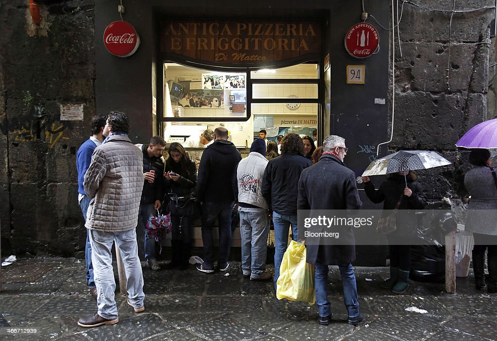Customers wait for their food orders outside a pizzeria take-away store on a side street in Naples, Italy, on Saturday, Feb. 1, 2014. In Naples, the local youth unemployment rate in 2012 was 53.6 percent compared to a national average of 35.3 percent. Photographer: Alessia Pierdomenico/Bloomberg via Getty Images