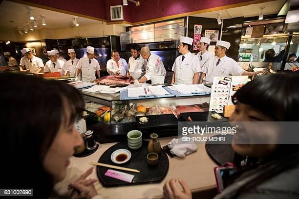 Customers wait for their order as employees of sushi restaurant chain SushiZanmai prepare a 212kilogram bluefin tuna at their restaurant near the...