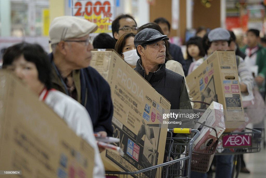 Customers wait in a check out line in an Aeon Co. shopping center in Tokyo, Japan, on Friday, Nov. 9, 2012. Aeon Co. is Japan's largest supermarket operator. Photographer: Akio Kon/Bloomberg via Getty Images
