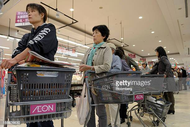 Customers wait in a check out line in an Aeon Co shopping center in Tokyo Japan on Friday Nov 9 2012 Aeon Co is Japan's largest supermarket operator...