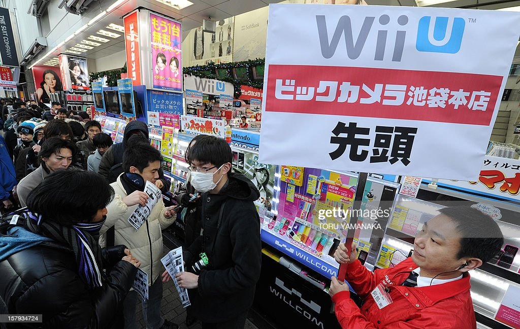 Customers wait in a line for the opening of a shop to purchase Japanese electronics titan Nintendo's new videogame console 'Wii U' in Tokyo on December 8, 2012. Nintendo released the new console in Japan on December 8 and is hoping for a repeat of the runaway success it had with original Wii consoles, which lured legions of 'casual gamers' into the videogame world with the introduction of motion-sensing controls. AFP PHOTO/Toru YAMANAKA