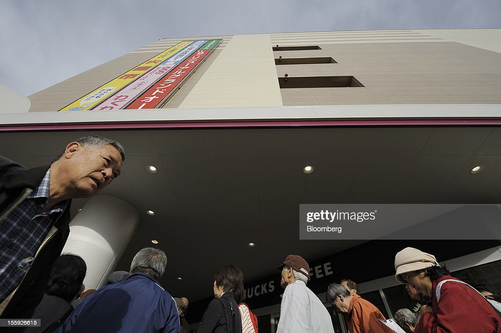 Customers wait in line for the opening of an Aeon Co. shopping center in Tokyo, Japan, on Friday, Nov. 9, 2012. Aeon Co. is Japan's largest supermarket operator. Photographer: Akio Kon/Bloomberg via Getty Images
