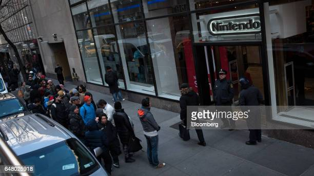 Customers wait in line outside of a Nintendo Co store to purchase the Nintendo Switch game console during the company's launch event in New York US...