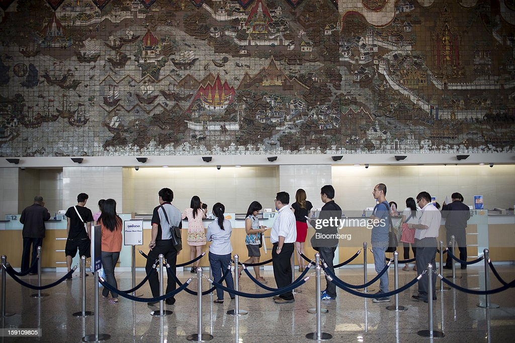 Customers wait in line to be served at the Bangkok Bank Pcl. headquarters in Bangkok, Thailand, on Tuesday, Jan. 8, 2013. Thailand's economy may have expanded 5.7 percent in 2012 and will grow 5 percent in 2013, the finance ministry said on Dec. 26. Photographer: Brent Lewin/Bloomberg via Getty Images