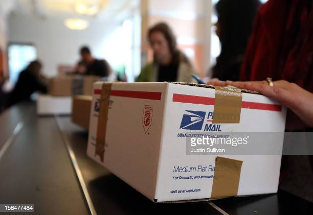 Customers wait in line to deliver packages at United States Post Office at Rincon Center on December 17 2012 in San Francisco California Customers...