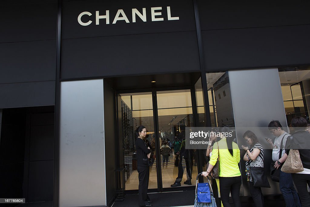 Customers wait in line to enter a Chanel SA store in the Tsim Sha Tsui area of Hong Kong, China, on Tuesday, April 30, 2013. Financial Secretary John Tsang on Feb. 27 projected annual growth of 1.5 percent to 3.5 percent this year following 2012's 1.4 percent, the weakest rate since 2009 as Europe's sovereign debt crisis sapped global demand. Photographer: Lam Yik Fei/Bloomberg via Getty Images