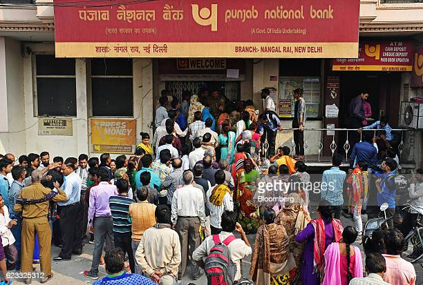 Customers wait in line to exchange Indian five hundred and one thousand rupee banknotes outside a Punjab National Bank branch in New Delhi India on...