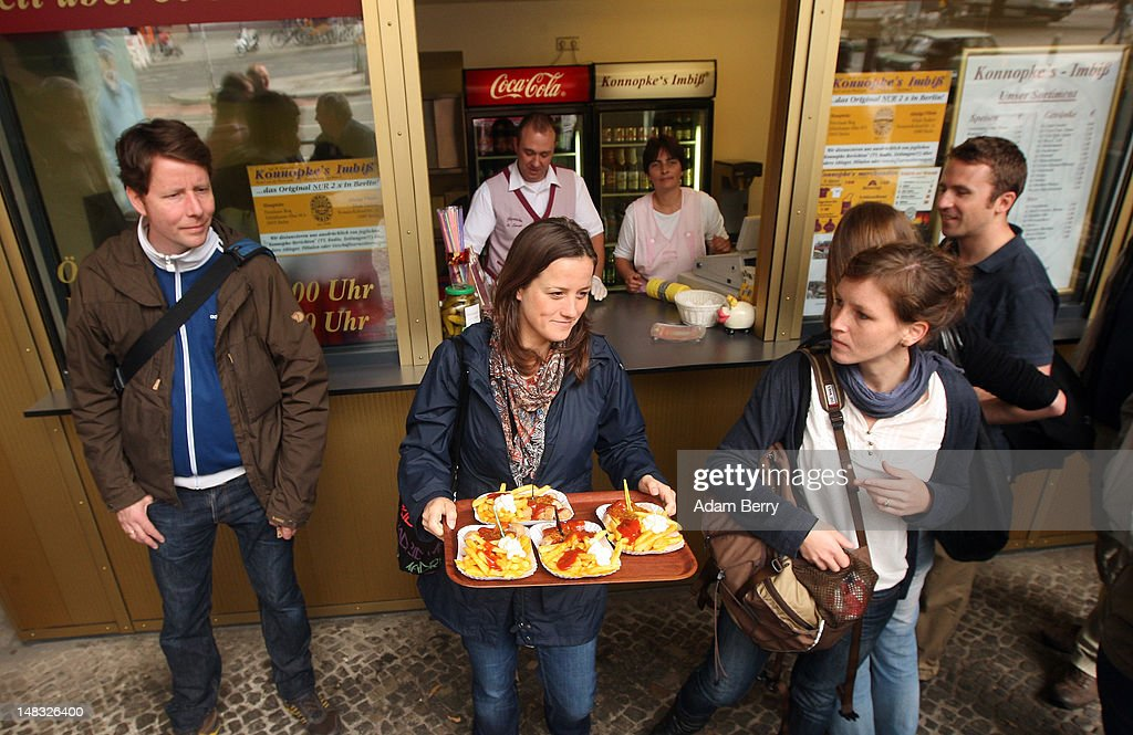 Customers wait in line to make purchases as another carries her meal at Konnopke's currywurst stand on July 14, 2012 in Berlin, Germany. Currywurst, originally founded in post-war Berlin by Herta Heuwa, is Berlin's answer to fast food and is sold at specialized stands across the city and the rest of Germany. Currywurst is pork sausage, with or without casing, fried or deep-fried, that is typically smothered in curry powder and a ketchup-like sauce called curry sauce and served with french fries.