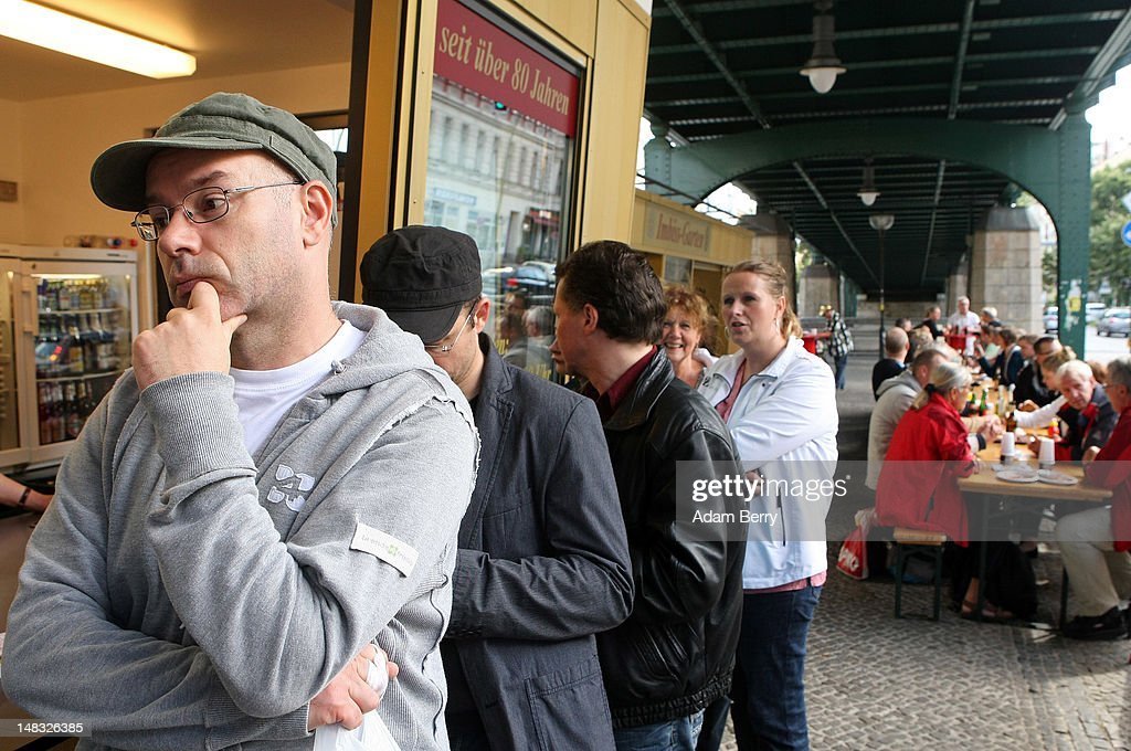 Customers wait in line to make purchases as others eat at Konnopke's currywurst stand on July 14, 2012 in Berlin, Germany. Currywurst, originally founded in post-war Berlin by Herta Heuwa, is Berlin's answer to fast food and is sold at specialized stands across the city and the rest of Germany. Currywurst is pork sausage, with or without casing, fried or deep-fried, that is typically smothered in curry powder and a ketchup-like sauce called curry sauce and served with french fries.