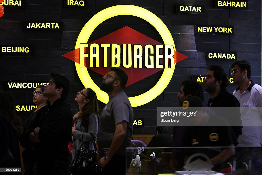 Customers wait in line to order at a Fatburger outlet in Karachi, Pakistan, on Saturday, Jan. 5, 2013. Fatburger opened its first outlet in Pakistan to the public on Jan. 5. Photographer: Asim Hafeez/Bloomberg via Getty Images