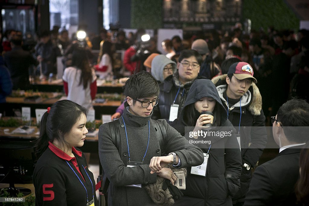 Customers wait in line to purchase the Apple Inc. iPhone 5 at a KT Corp. Olleh brand mobile phone store in Seoul, South Korea, on Friday, Dec. 7, 2012. The iPhone 5 went on sale in South Korea today. Photographer: Jean Chung/Bloomberg via Getty Images