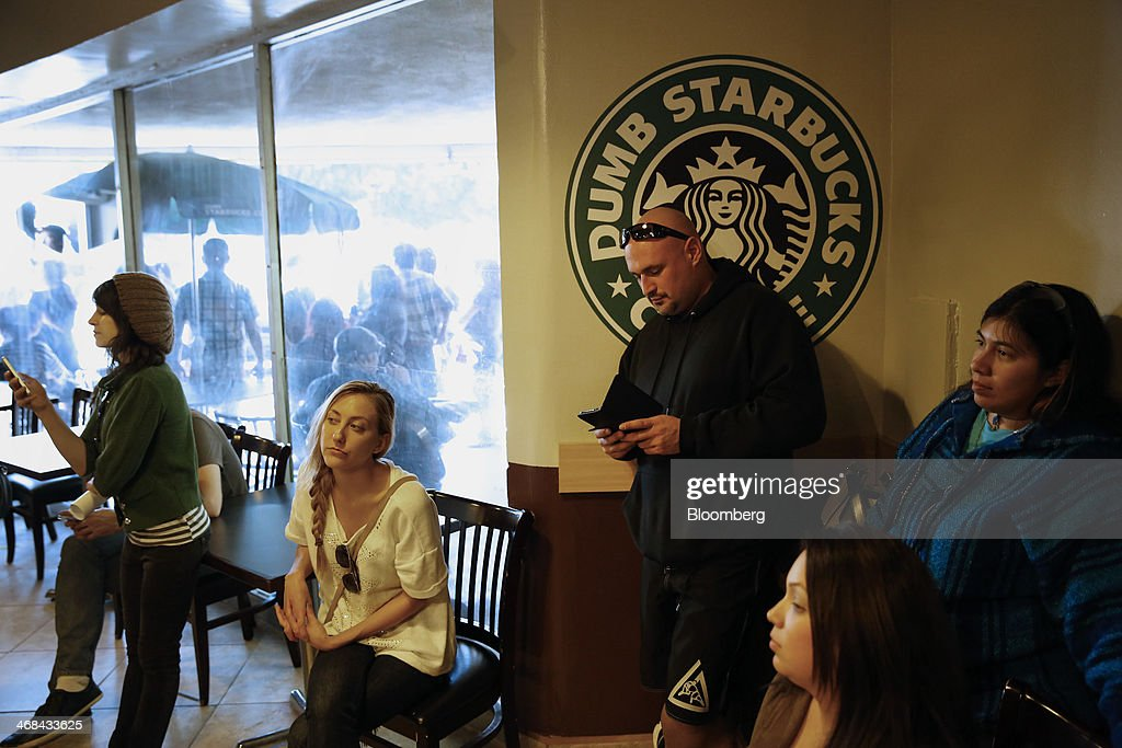 Customers wait in line to receive coffee at the Dumb Starbucks Coffee store, a parody of the Starbucks Corp. coffee chain, in Los Angeles, California, U.S., on Monday, Feb. 10, 2014. Dumb Starbucks, which opened this past weekend, offered Dumb Vanilla Blonde Roast, Dumb Chai Tea Latte, and Dumb Caramel Macchiato, all available in sizes Dumb Venti, Dumb Grande, and Dumb Tall. Photographer: Patrick T. Fallon/Bloomberg via Getty Images