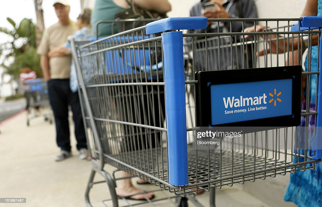 Customers wait in line with shopping carts for the grand opening of a new Wal-Mart Stores Inc. location in Torrance, California, U.S., on Wednesday, Sept. 12, 2012. The Wal-Mart store, which was the first location to open in Los Angeles County since 2006, was built inside of a former Mervyn's clothing location. Photographer: Patrick Fallon/Bloomberg via Getty Images