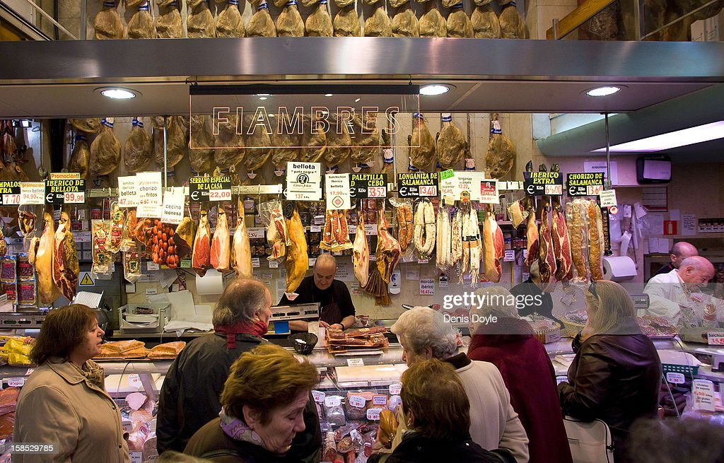 Customers wait to be attended at the Ferpal ham store on Calle Arenal on December 18, 2012 in Madrid, Spain. Dry-cured Iberian ham or Jamon Iberico is a favourite amongst Spaniards and producers are hoping for improved sales over the busy Christmas period. The jamon Iberico de Bellota are usually dry-cured for up to three years after the pigs have been few on a diet of acorns in the last three months of their lives.