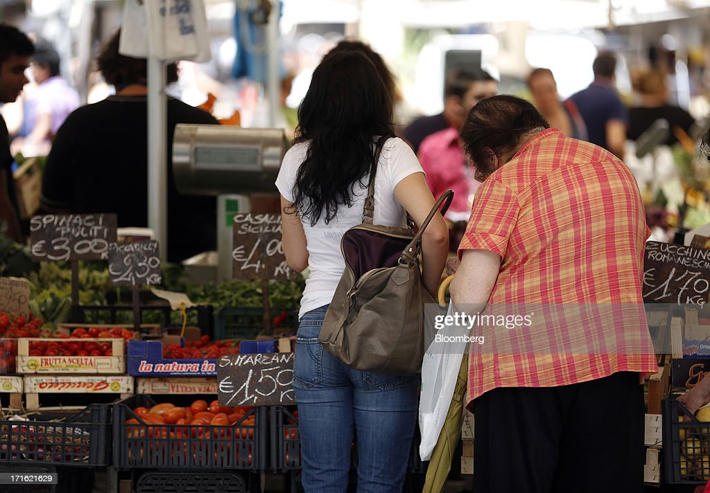Customers wait to be served at a fruit and vegetable stall at an outdoor market in Rome, Italy, on Wednesday, June 26, 2013. Italian household confidence rose this month as consumers grew optimistic about the country's outlook as Prime Minister Enrico Letta's government plans to cut taxes and boost youth employment. Photographer: Alessia Pierdomenico/Bloomberg via Getty Images