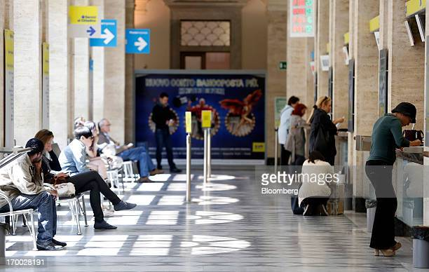 Customers wait to be served inside a Poste Italiane SpA post office in Rome Italy on Wednesday June 5 2013 Rome based Poste Italiane boosted 2012...