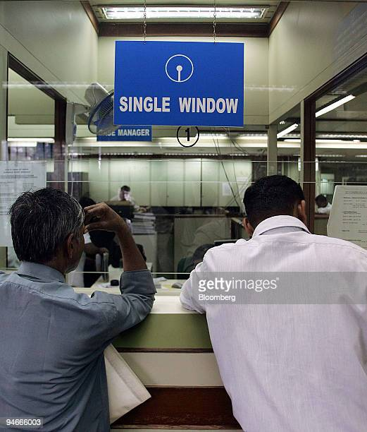 Customers wait to carry out their bank transactions inside a branch of the State Bank of India at Nariman Point Mumbai on Tuesday July 11 2006 Indian...