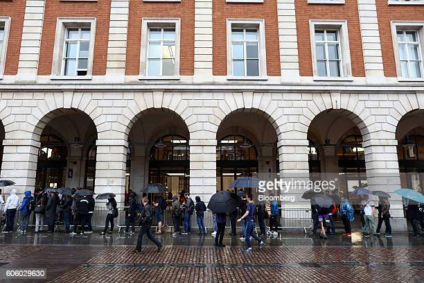 Customers wait to collect preordered new iPhone 7 smartphones outside the Apple Inc Covent Garden store in London UK on Friday Sept 16 2016 Consumers...