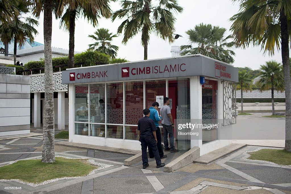 Customers wait to use a CIMB Group Holdings Bhd. automated teller machine (ATM) located outside the National Mosque of Malaysia in Kuala Lumpur, Malaysia, on Tuesday, July 22, 2014. CIMB, RHB Capital Bhd. and the Malaysia Building Society Bhd. won central bank approval to proceed with merger talks that would create a 'mega Islamic bank,' they said in a July 10 statement. Photographer: Brent Lewin/Bloomberg via Getty Images