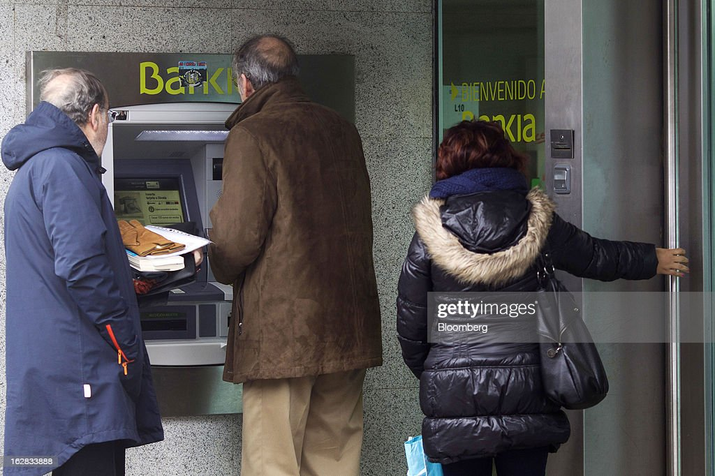 Customers wait to use automated teller machines (ATM) outside a Bankia SA branch in Madrid, Spain, on Thursday, Feb. 28, 2013. BFA-Bankia Chairman Jose Ignacio Goirigolzarri said a balance sheet clean-up that inflicted a 21.2 billion-euro ($27.6 billion) after-tax loss last year will set the Spanish banking group on course to repay state aid. Photographer: Angel Navarrete/Bloomberg via Getty Images