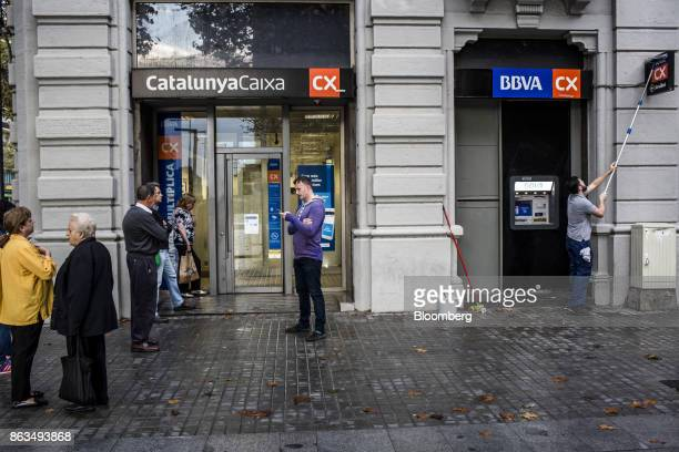 Customers wait to withdraw cash from a Catalunya Bank SA bank branch as a worker cleans a sign above a Banco Bilbao Vizcaya Argentaria SA automated...