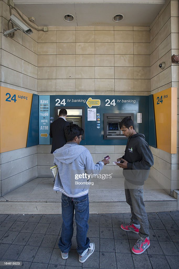 Customers wait to withdraw cash from an automated teller machine (ATM) operated by the Bank of Cyprus Plc in Nicosia, Cyprus, on Monday, March 25, 2013. Cyprus dodged a disorderly default and unprecedented exit from the euro by bowing to demands from creditors to shrink its banking system in exchange for 10 billion euros ($13 billion) of aid. Photographer: Simon Dawson/Bloomberg via Getty Images