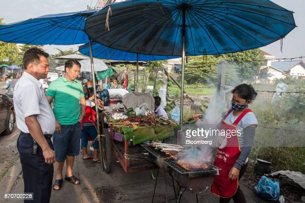 Customers wait while a vendor grills meat at a morning market in Vientiane Laos on Thursday Nov 2 2017 Located in the Mekong region Southeast Asia's...