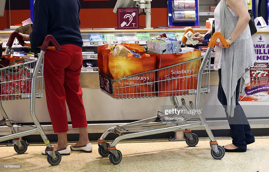 Customers wait with loaded shopping carts at a lottery and cigarette kiosk inside a Sainsbury's supermarket store, operated by J Sainsbury Plc, in Godalming, U.K., on Thursday, May 2, 2013. J Sainsbury Plc, the U.K.'s third-largest supermarket chain, will report full year results on May 8. Photographer: Chris Ratcliffe/Bloomberg via Getty Images