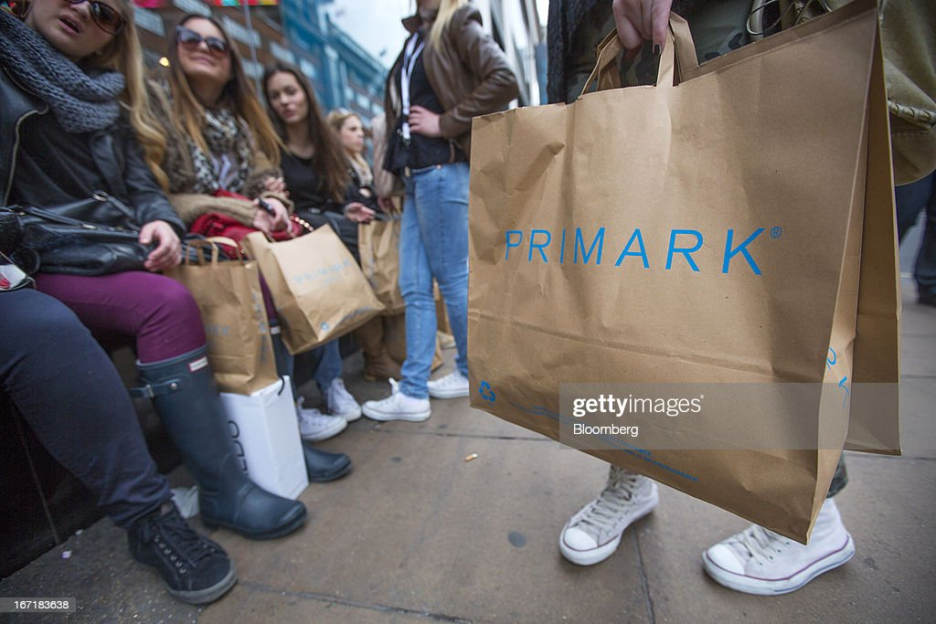 Customers wait with their shopping bags outside a Primark store on Oxford Street in central London, U.K., on Monday, April 22, 2013. Associated British Foods Plc, the owner of the Primark discount-clothing chain, fell the most in three months after Credit Suisse Group AG said it's unlikely the chain's profit growth can continue at the first half's pace. Photographer: Jason Alden/Bloomberg via Getty Images