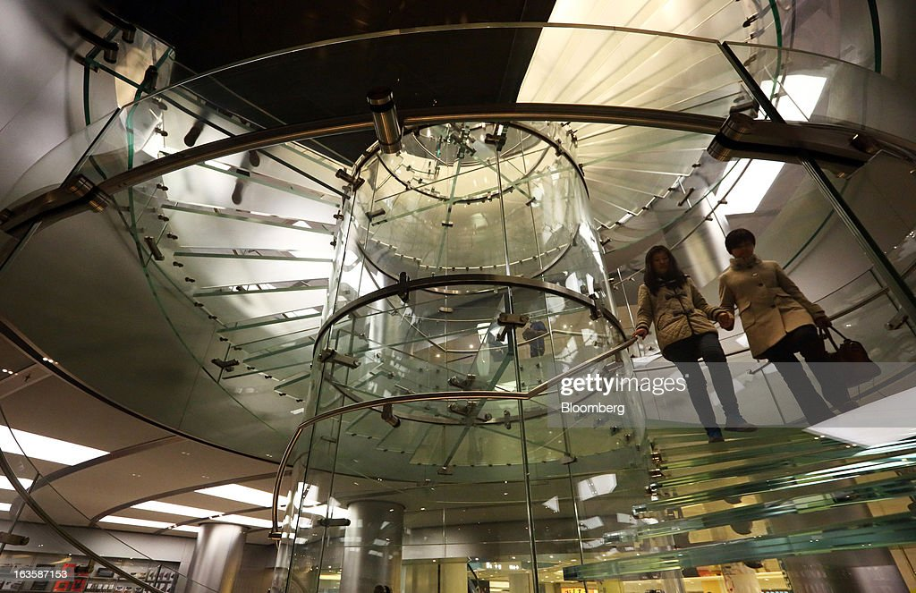 Customers walk down a spiral staircase at the Apple Inc. store in the Wangfujing area of Beijing, China, on Tuesday, March 12, 2013. Apple's Wangfujing store is the largest in Asia. Photographer: Tomohiro Ohsumi/Bloomberg via Getty Images