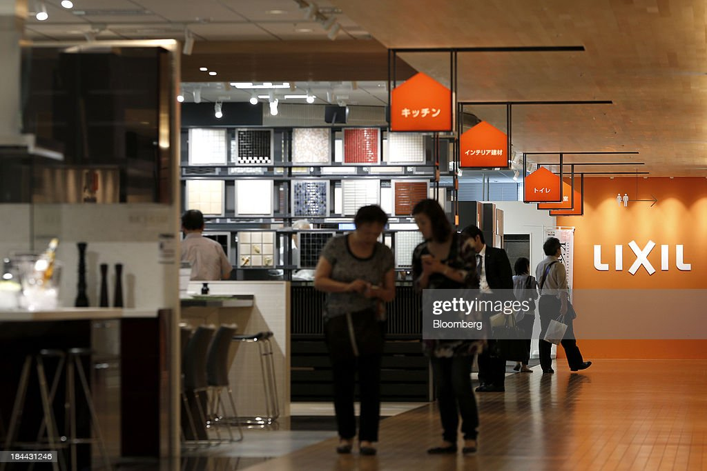 Customers walk in front of the Lixil Group Corp. logo at the company's showroom in Tokyo, Japan, on Friday, Oct. 11, 2013. Lixil and Development Bank of Japan agreed on Sept. 26 to buy bathroom-fixtures maker Grohe Group, valuing the German company at 3.06 billion euros ($4.1 billion). Photographer: Kiyoshi Ota/Bloomberg via Getty Images