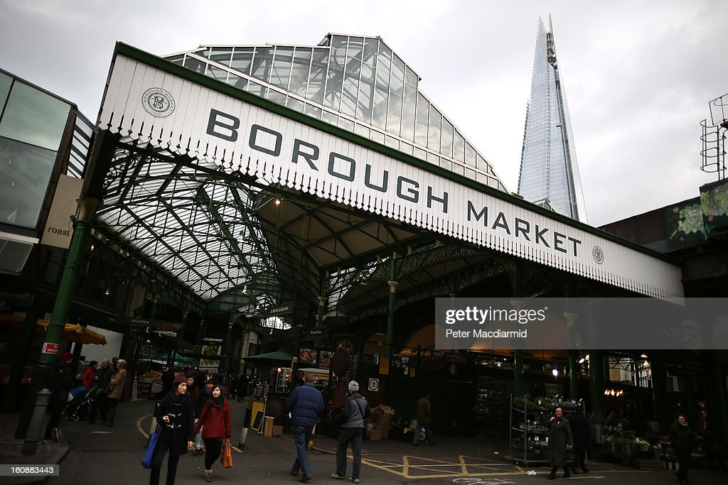 Customers walk into Borough Market in sight of The Shard skyscraper on February 7, 2013 in London, England. Borough Market, London's oldest since 1756, has recently completed renovation and today had it's first day of full trading.